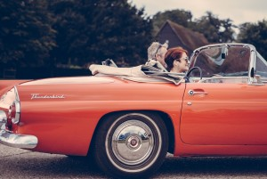Couple riding in a red Thunderbird with the top down. Photo by Clem Onojeghuo on Unsplash