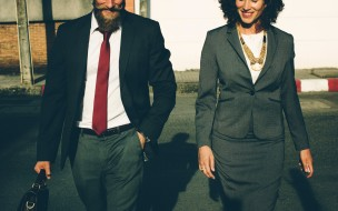 A photo of a happy business man and business woman walking. Photo credit rawpixel.com